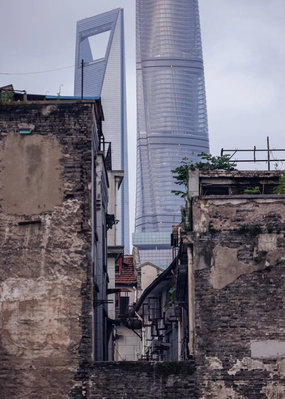 Skyscrapers tower over crumbling brick lane houses