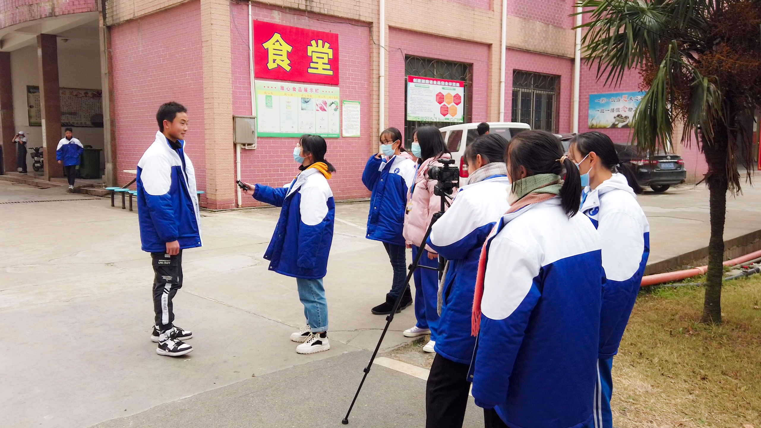 Uniformed students with camera and recorder interview classmate in front of school cafeteria