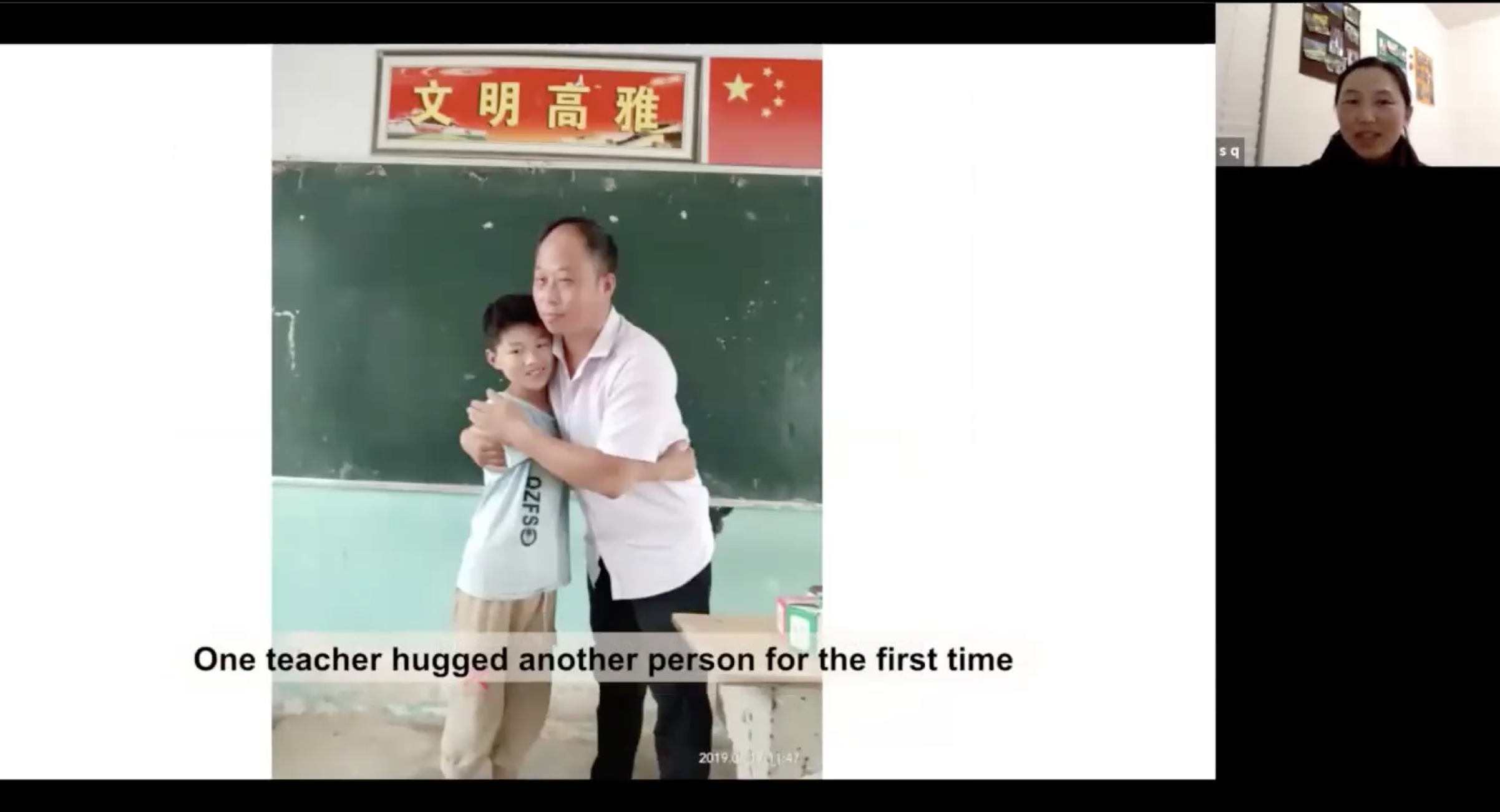 Teacher hugs young student in front of classroom blackboard