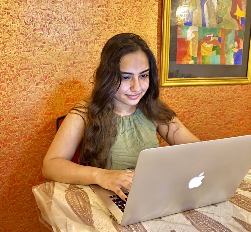 Damya Bhatia sits at a desk working on her computer for her remote internship