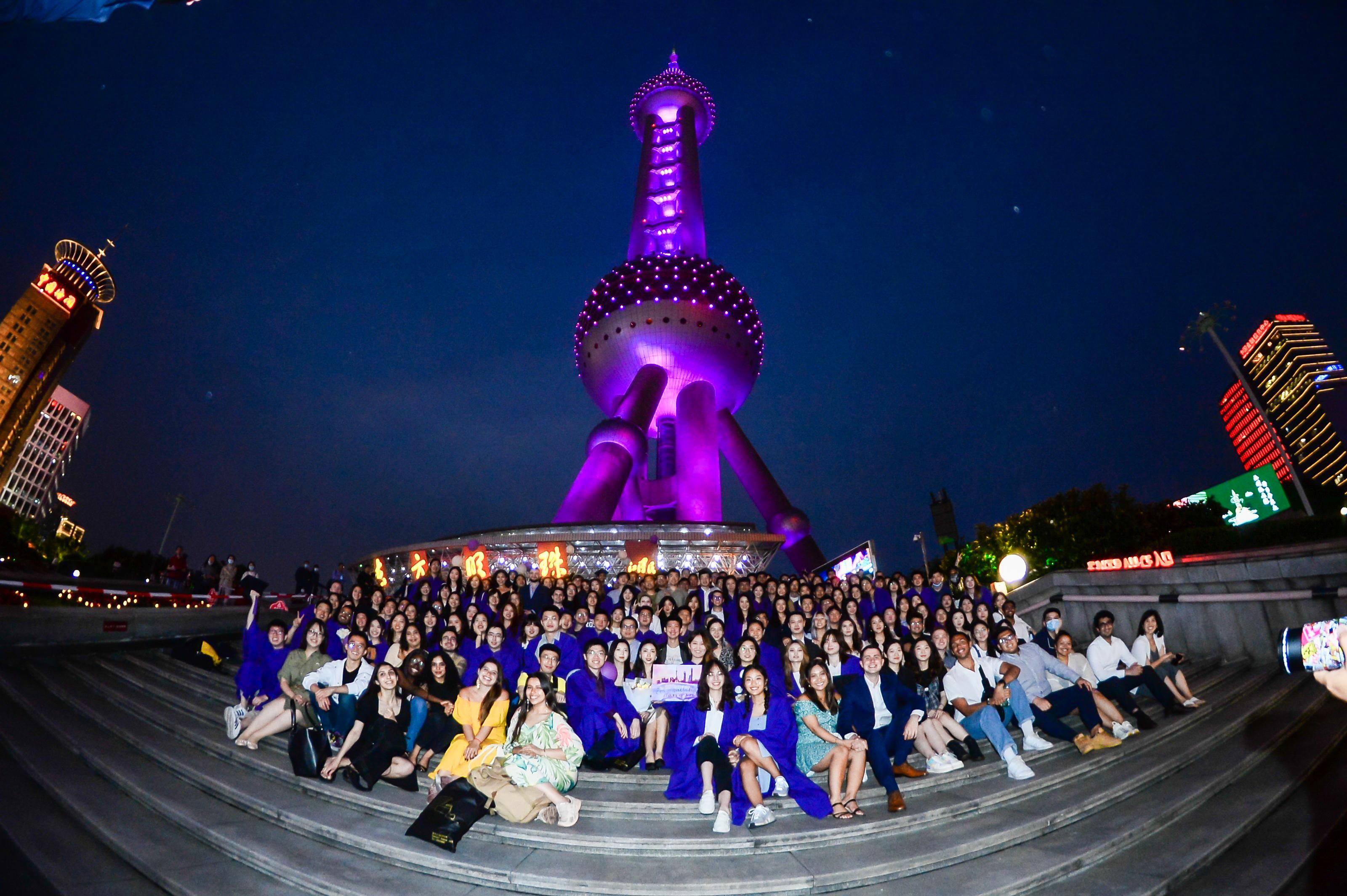 Graduates line steps at base of purple Oriental Pearl Tower