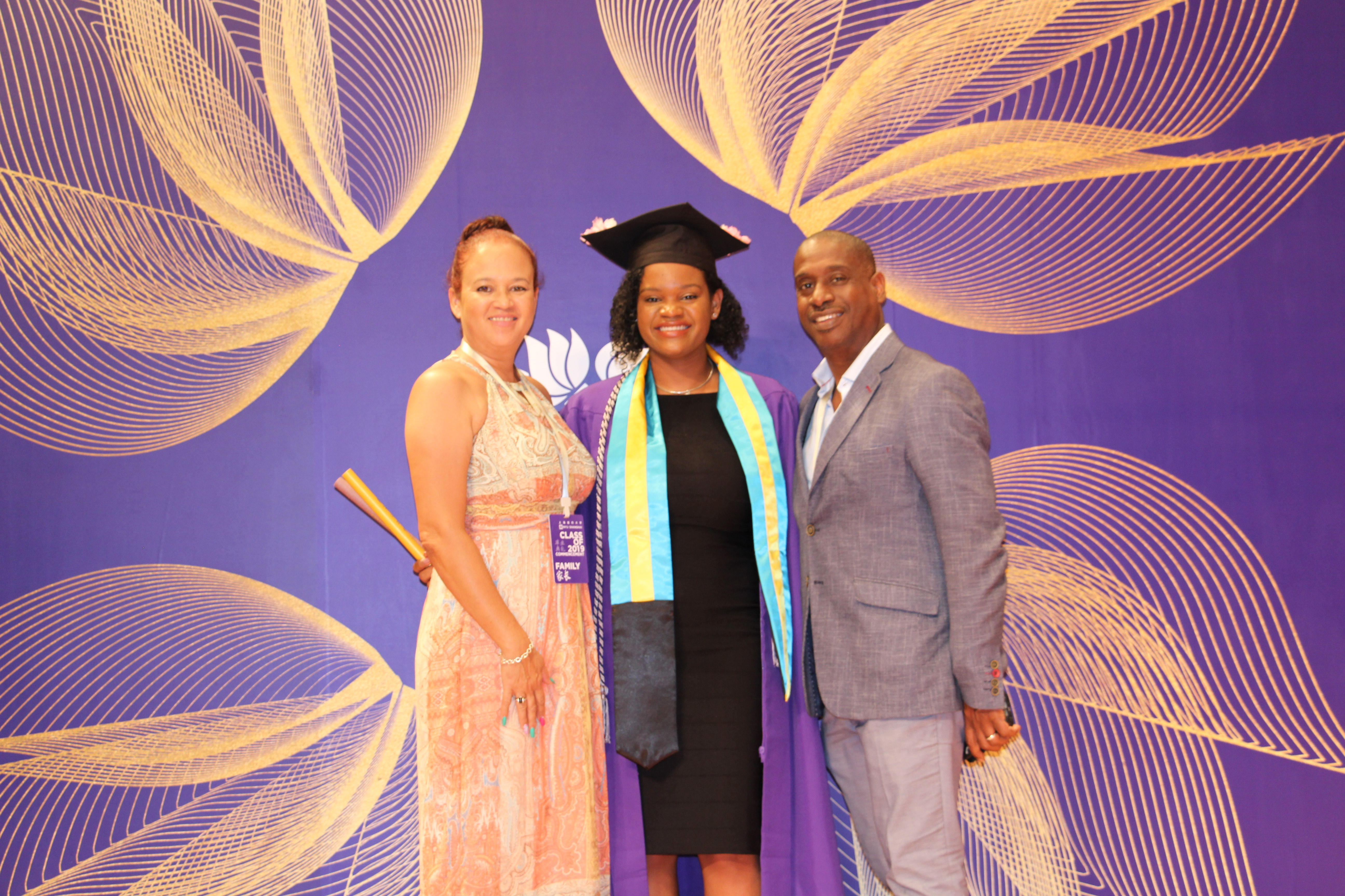 Glinton poses with her parents in NYU Shanghai graduation robes
