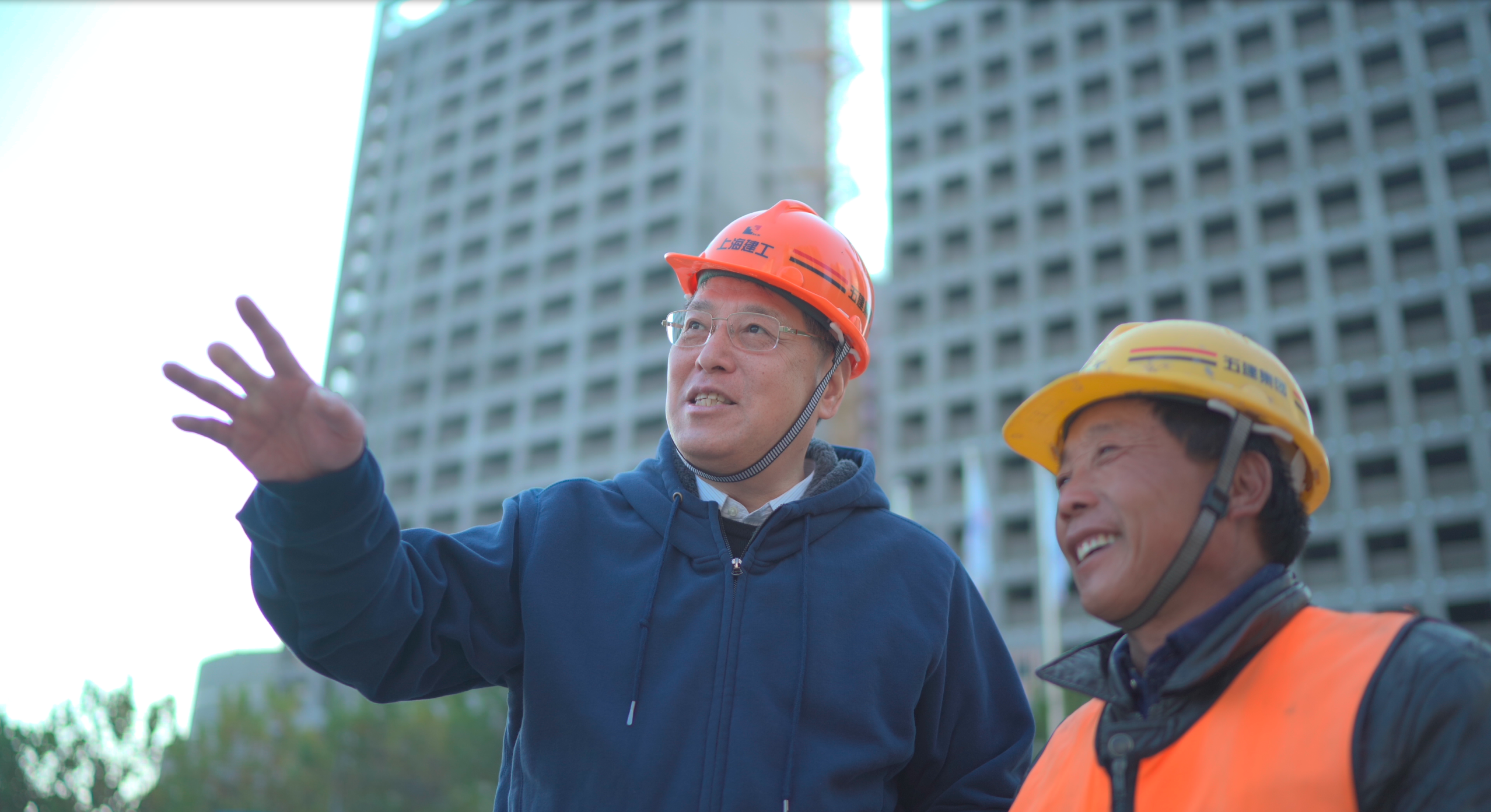 Yu, wearing hardhat, talks with construction worker at Qiantan campus building site