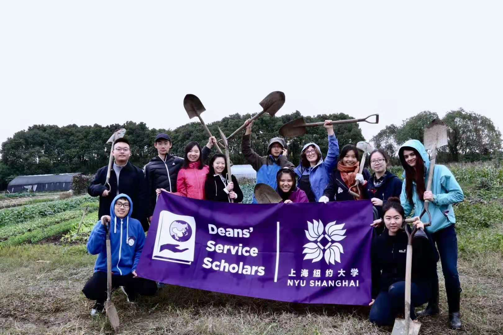 Ma and fellow volunteers wave shovels and pose in field with NYU Shanghai purple banner