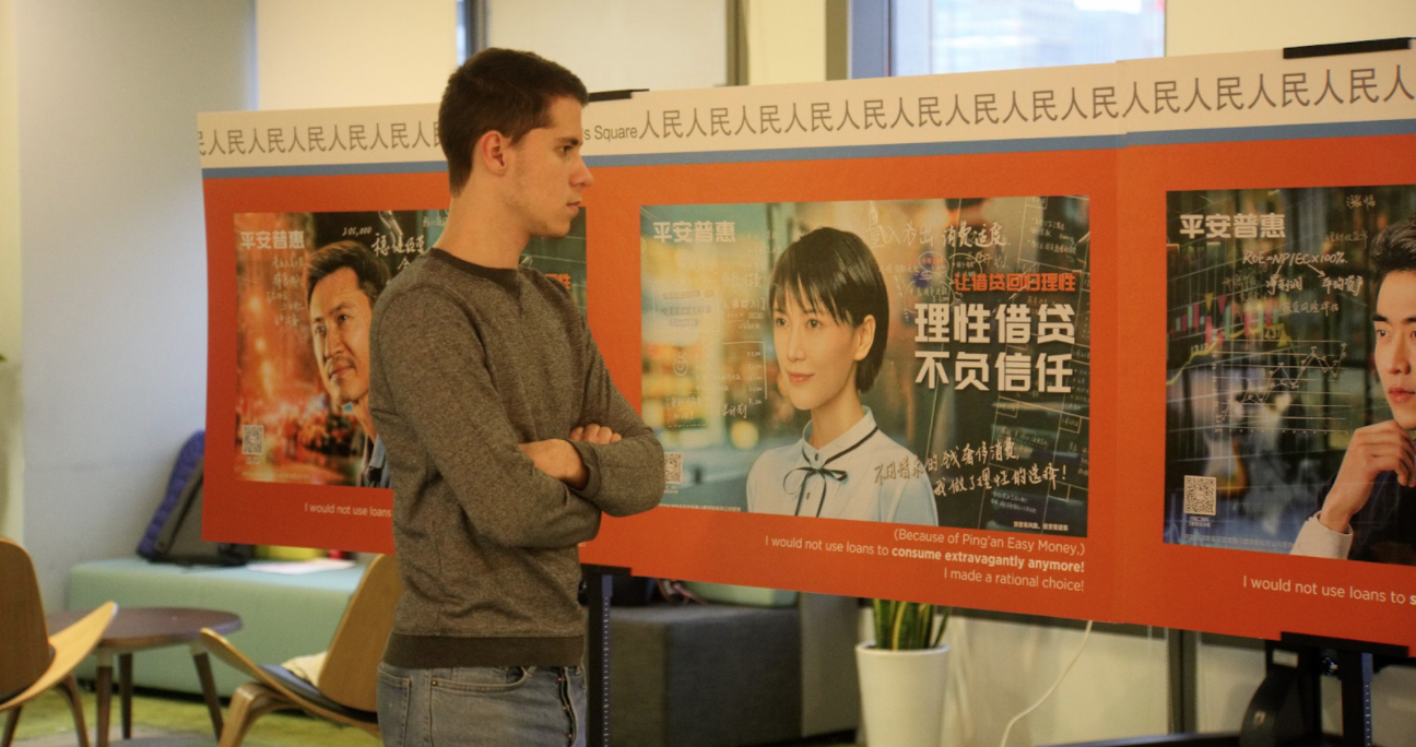 Student looks at poster presenting marketing images