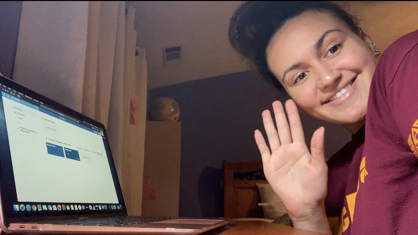 Tenielle Ellis waves at the camera while working at her laptop from home