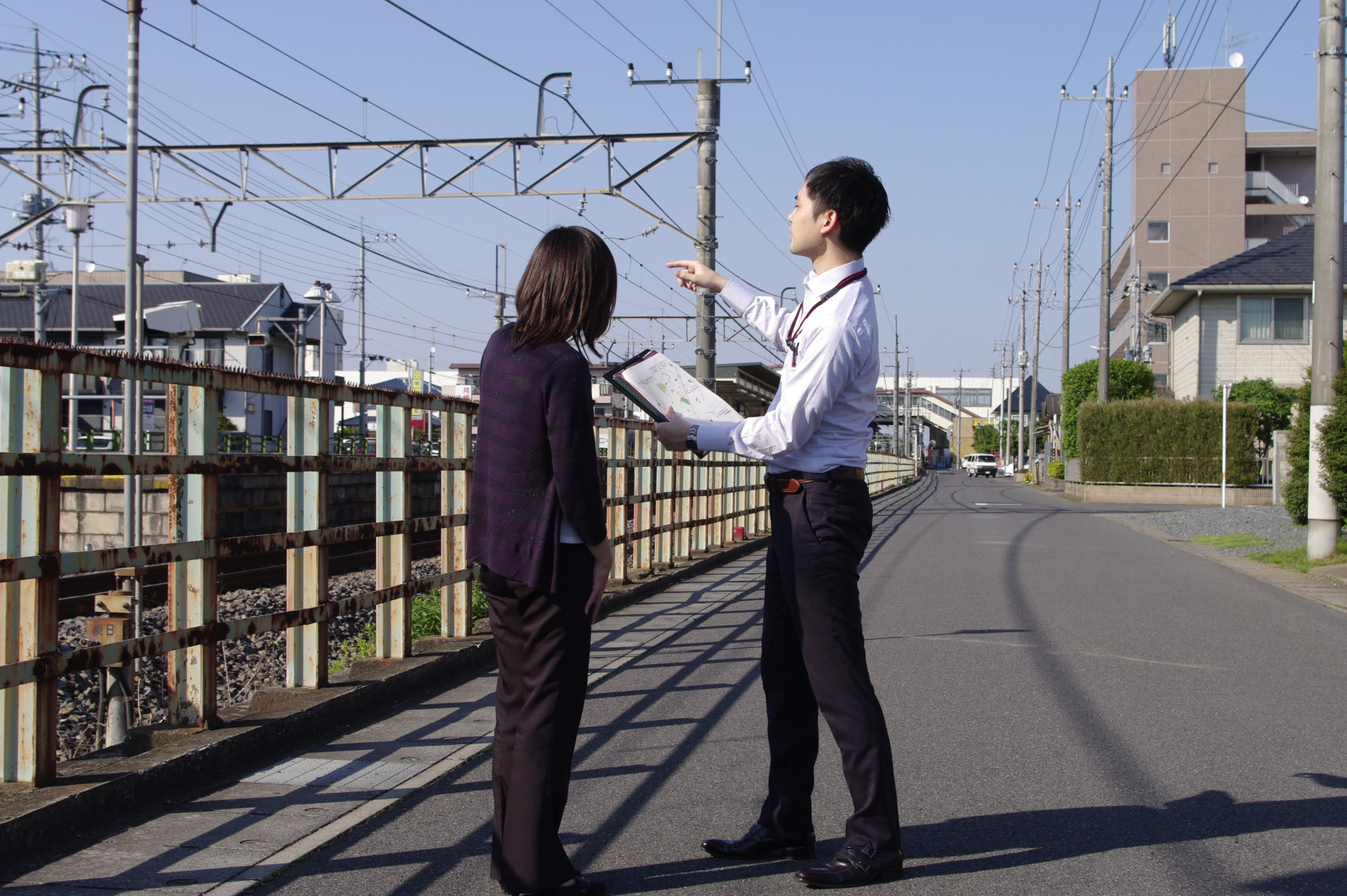 Haginoya discussing the environment of a crime site with an investigator in Japan