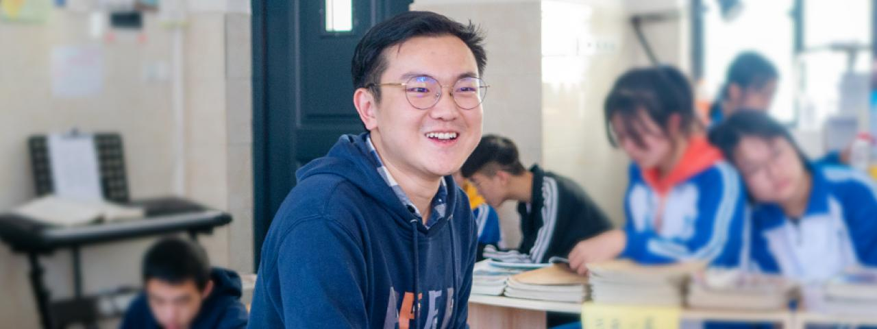 Shi laughs in classroom surrounded by students reading and writing