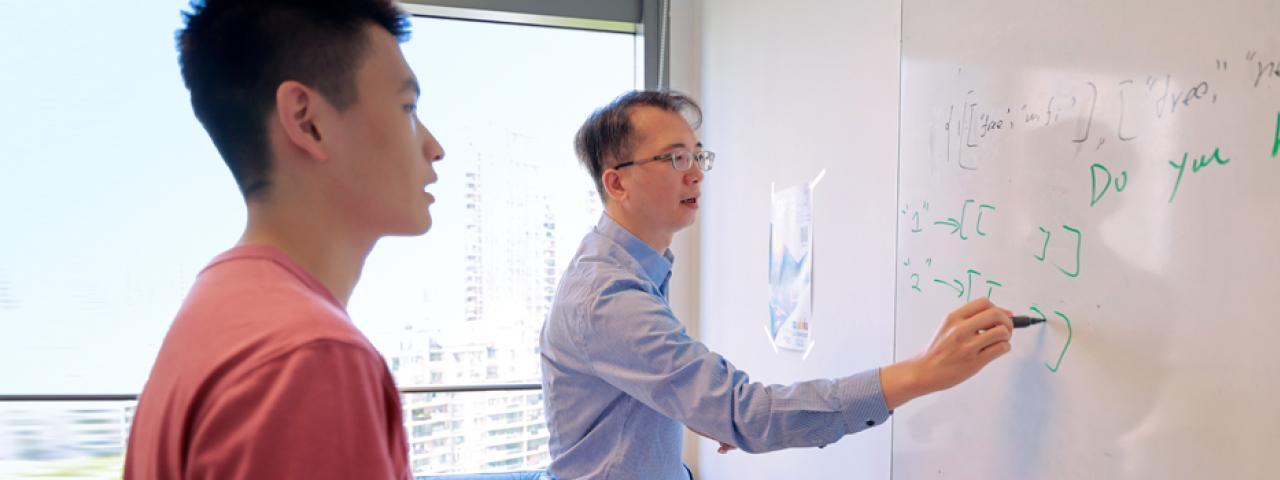 Tam demonstrates coding solution on whiteboard for student