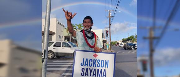 Sayama waves a sign under a rainbow