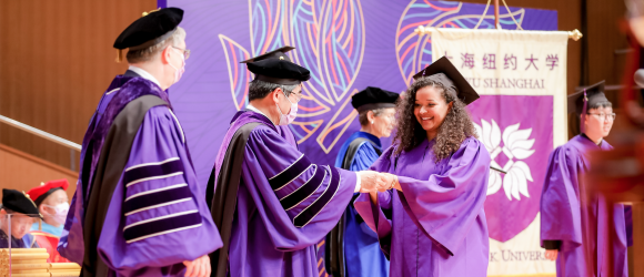 Graduate accepts diploma from Chancellor