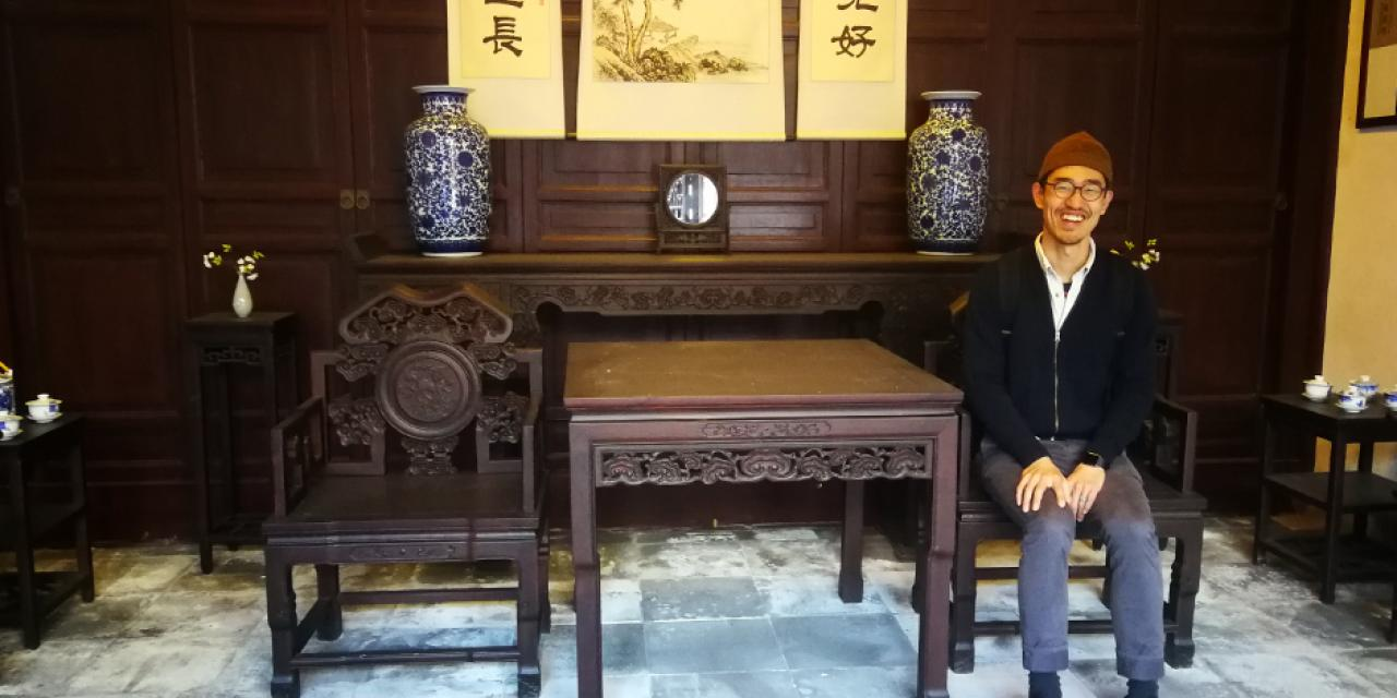Vincent Qian from Community Engaged Learning tries out some of the furniture inside the Residence of Li.