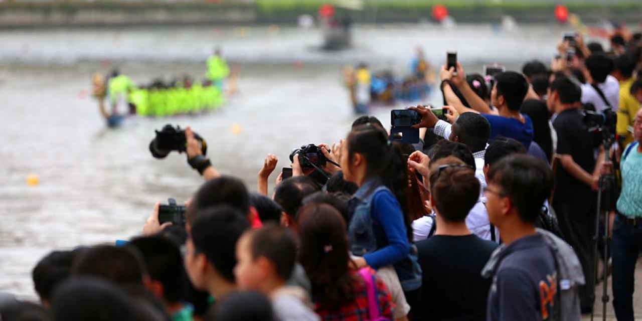 Crowds gather to cheer on participants of Shanghai's annual Dragon Boat Races held at Suzhou Creek. Teams participating in the race consisted of both international and Chinese rowers. During the Dragon Boat Festival many Chinese families prepare and eat Zongzi, a pyramid shaped rice dumpling traditionally filled with pork and other dried fruits. (Photo by: Dylan J Crow)