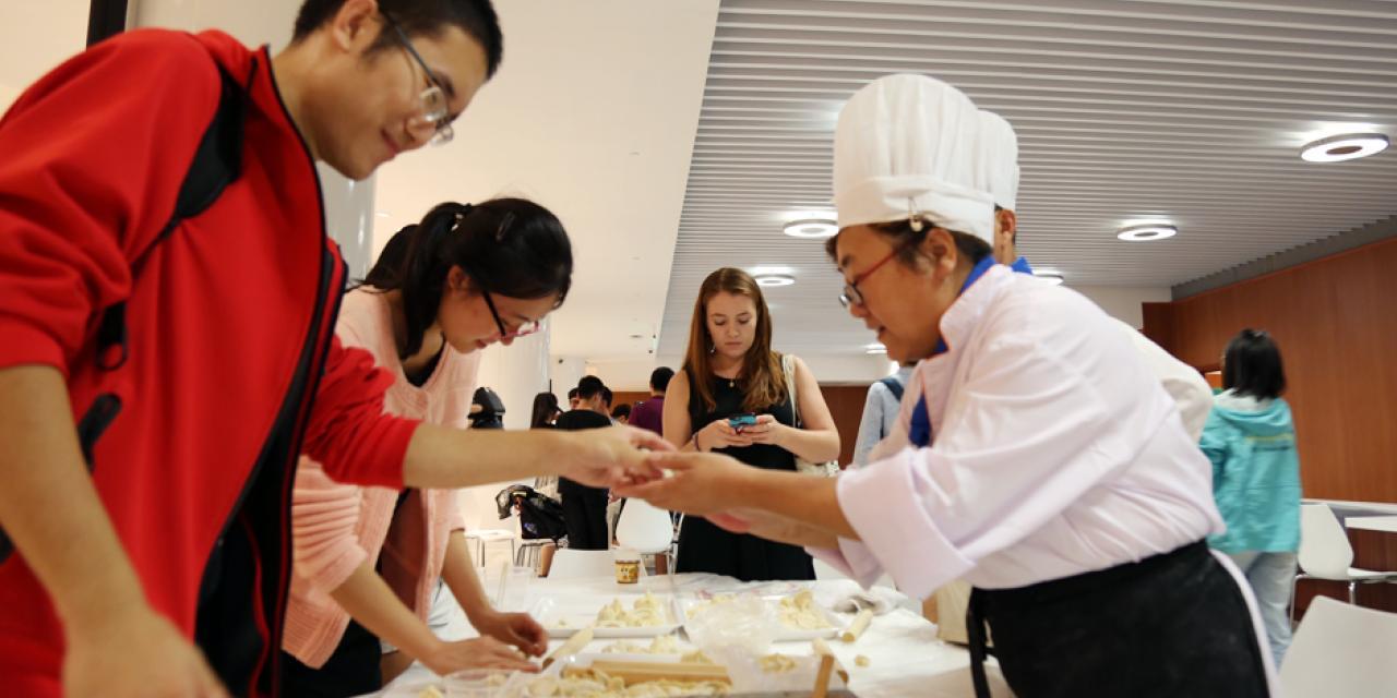 """9月28日,一年一度的上纽大""""饺子节""""又登场了!学校餐厅准备了一万个饺子, 让同学们品尝到各种馅料的饺子。国际学生还忙着向大厨学包饺子。这项也许只有在中国才能get到的技能,一定会在今后让他们在自己的国家和世界各地发扬光大。(摄影:胡文倩)"""