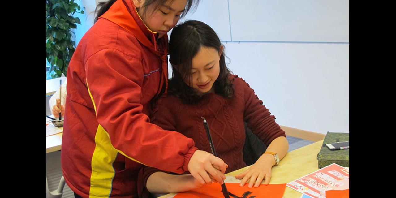 上海纽约大学学生庆祝中国新年,外国学生学习中国传统文化,与中国学生一起参与剪纸、书法、名族舞以及中国传统游戏。(摄影:NYU Shanghai)