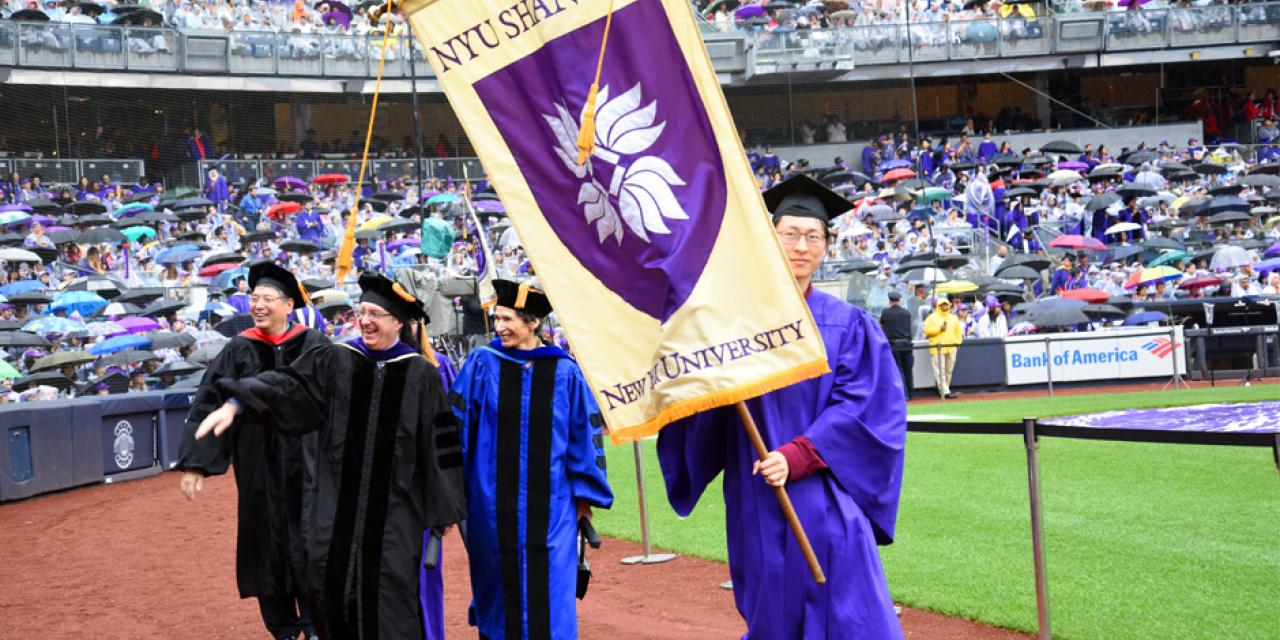 NYU Shanghai graduate Su Han'18 carried the banner for the university, alongside representatives from all of NYU's schools and campuses ( Photo by: Leo Sorel )