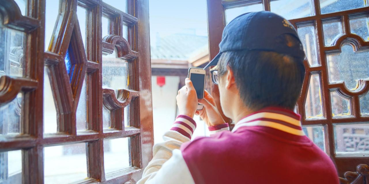 Interactive Media and Business major Murray Lu '22 photographs windows inside the residence. The tour of the residence was led by Wang Huizhu, a local retiree and volunteer guide who explained that the clear window panes used to be made of stained glass, but now only small pieces of colored glass remain.