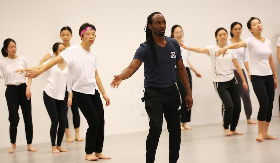 DCDC was founded 50 years ago in Dayton, Ohio, to create performance opportunities for dancers of color and remains rooted in the African American experience. At NYU Shanghai, dancers introduced students to Nigerian dance steps and music. DCDC's Devin Baker (center), shows students how to convey emotion through arm movements.