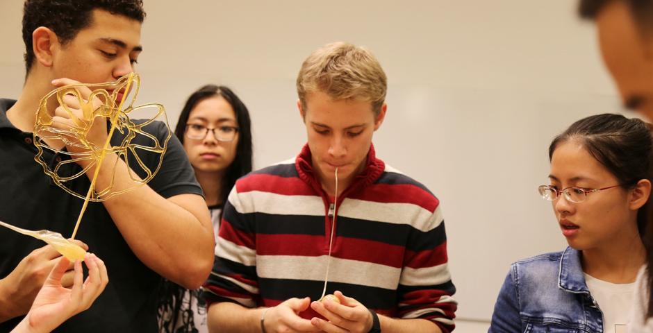 10月26日,两位中国传统艺术大师指导上纽大学生学习画糖画。用糖稀写字、作画,栩栩如生的动物跃然呈现,这就是民间工艺的艺术魅力。(摄影:胡文倩)