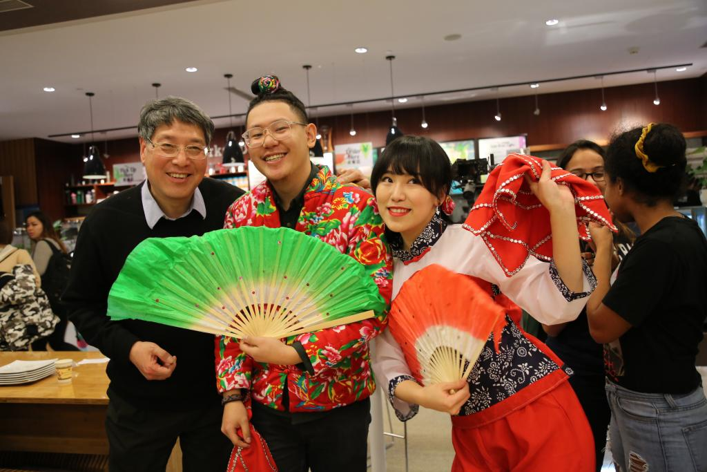 Chancellor Yu, Rudy Song '19, and Feng Zhe '20 pose with traditional Chinese dance props.