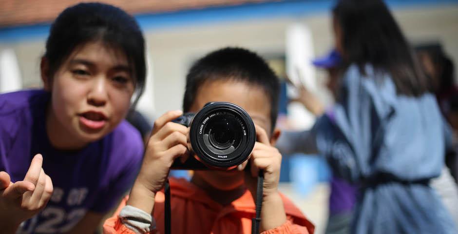 Wen Tao '22 gives a local child a hands-on tutorial on using a digital camera. (Photo by Takumi Miyawaki, NYU AD '20)