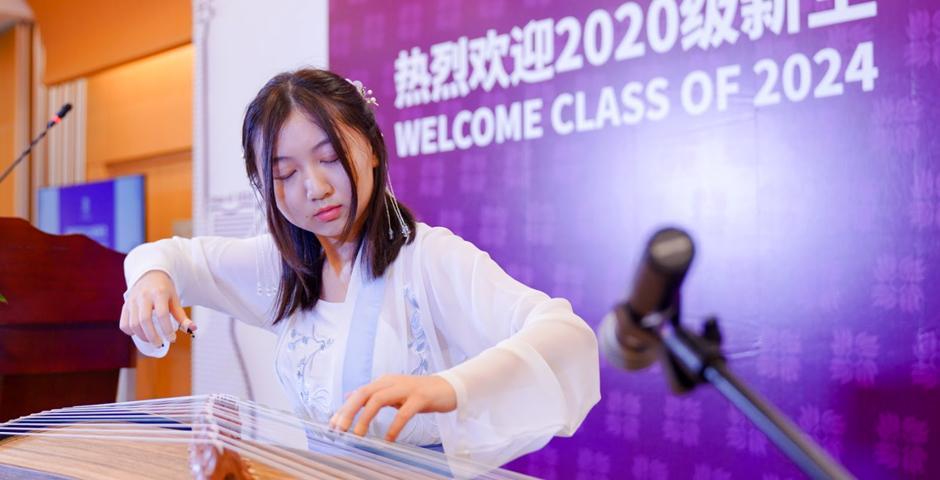 """开学典礼上,2023届学生冯泊宁用古筝弹奏了一曲唐朝古乐《将军令》。今年迎新活动的主题为""""琴"""",取自""""琴棋书画""""四艺。该词常用以表示学者的文化素养深厚。作为一所秉承博雅教育理念的中国高校,上海纽约大学鼓励学生了解、挖掘、培养自己的各项才能。"""