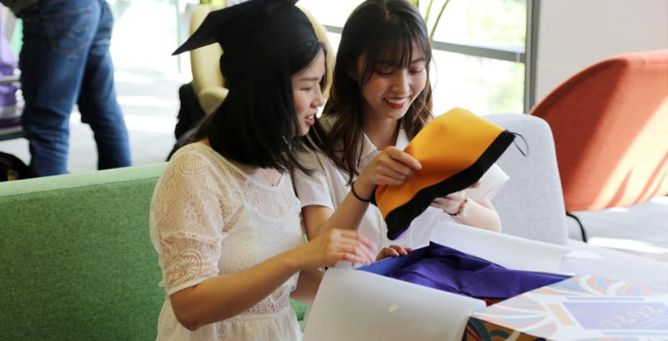 Quantitative Finance graduates, Yijin Chen MS '20 (left) and Chenyi Lu MS '20 (right), open their gift boxes in the 5th Floor Graduate Lounge.