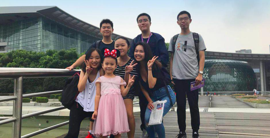 Some of the challenges required freshmen to engage with members of the public. Here a team pose for a group picture with a Chinese girl. (Photo by: NYU Shanghai)