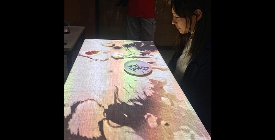 """其中,""""互动餐桌""""——""""箸"""",由互动媒体艺术专业的四位2018届学生姚毓夏、赵艺、赵楠和王玮钰联合创作。借助筷子这一工具,将中式用餐体验与传统文化结合起来,引人入胜。互动媒体艺术助教杜佳东设计的机器人Minus E,将机械作画提升到一个新的境界,将输入的图片在降低像素后,用白板笔重新画出。(摄影: Leon Lu & 陈梦竹)"""