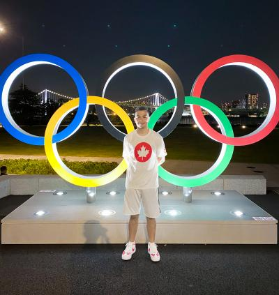 Hazin stands in front of Olympic rings against Tokyo skyline